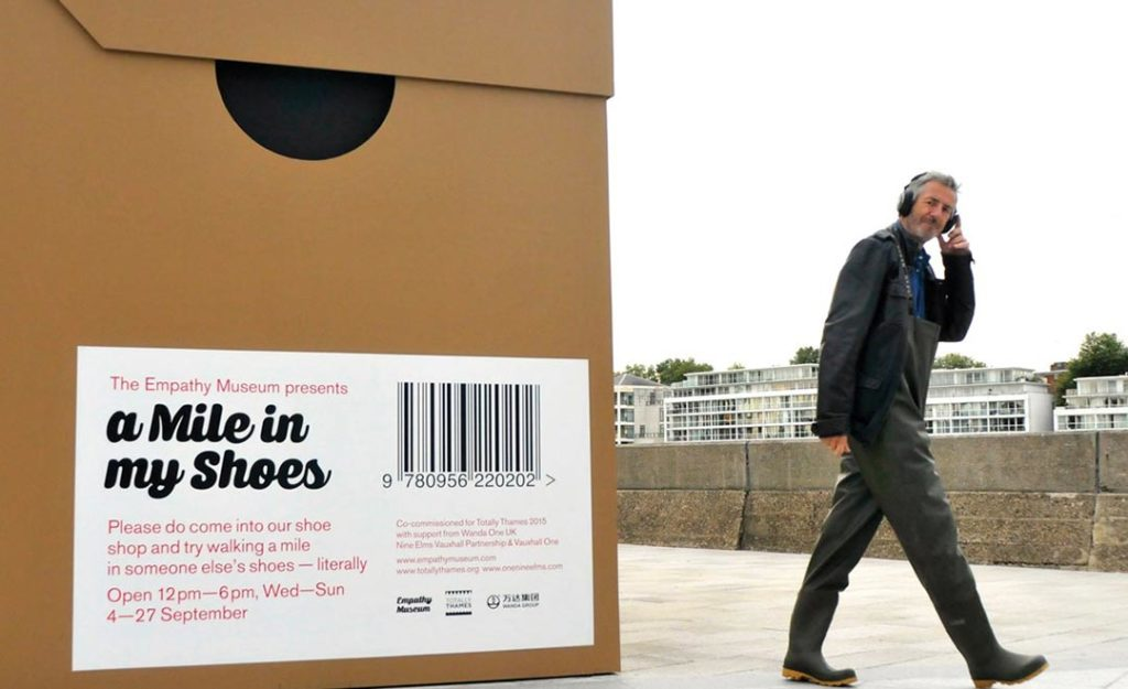 A man walking with headphones on next to a giant shoe box