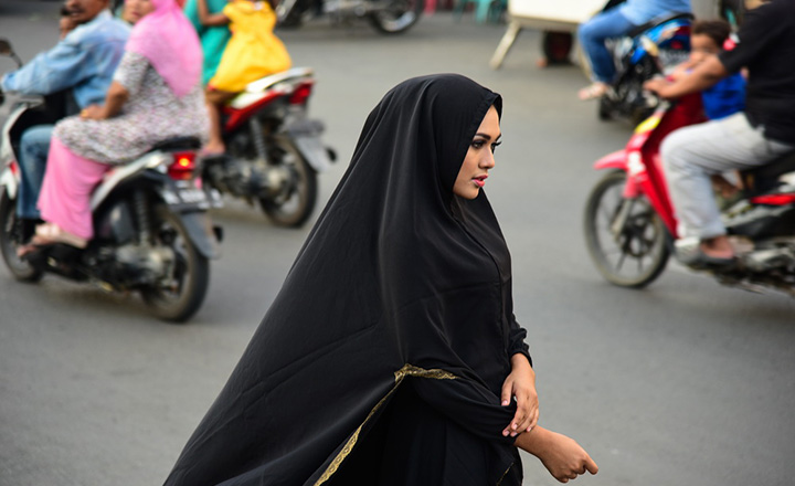 A woman walking on a street wearing a hijab