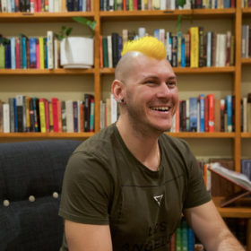 A man with a bright yellow mohawk smiling