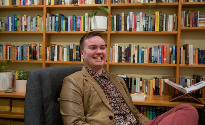 A young man wearing a beige blazer smiling by a bookshelf