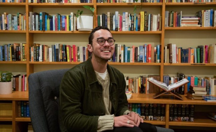 A young man wearing glasses smiling by a bookshelf
