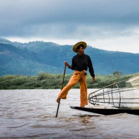 A photograph by Ann Jones of a man standing on a boat on the river