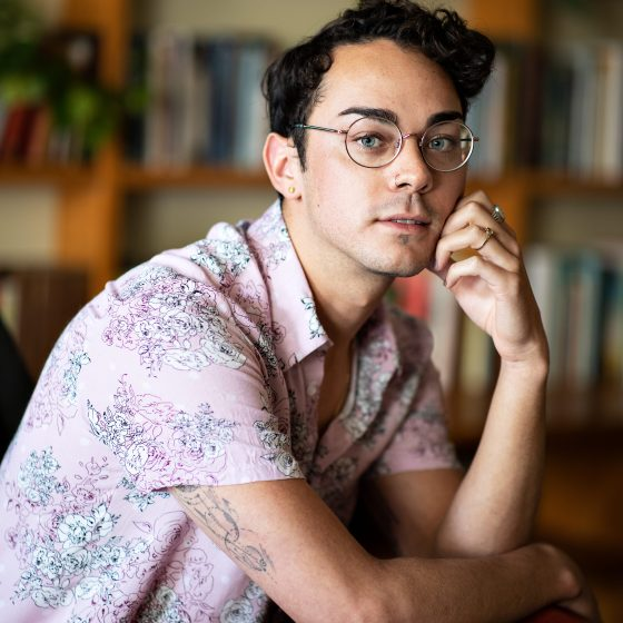 An absolutely stunning portrait of quite possibly the most handsome young man in Perth, Jay Anderson. He sits in the Centre for Stories library with his hand resting gently on his chin. His hair is perfectly quiffed and he wears golden-rimmed round glasses.