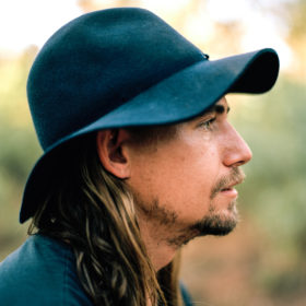 A profile shot of a man in the outback wearing a black wide-brimmed hat