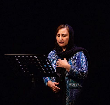 A woman wearing a headscarf and performing her story