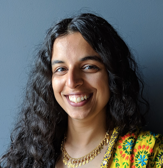 A photograph of Sukhjit smiling and wearing a lovely yellow top.