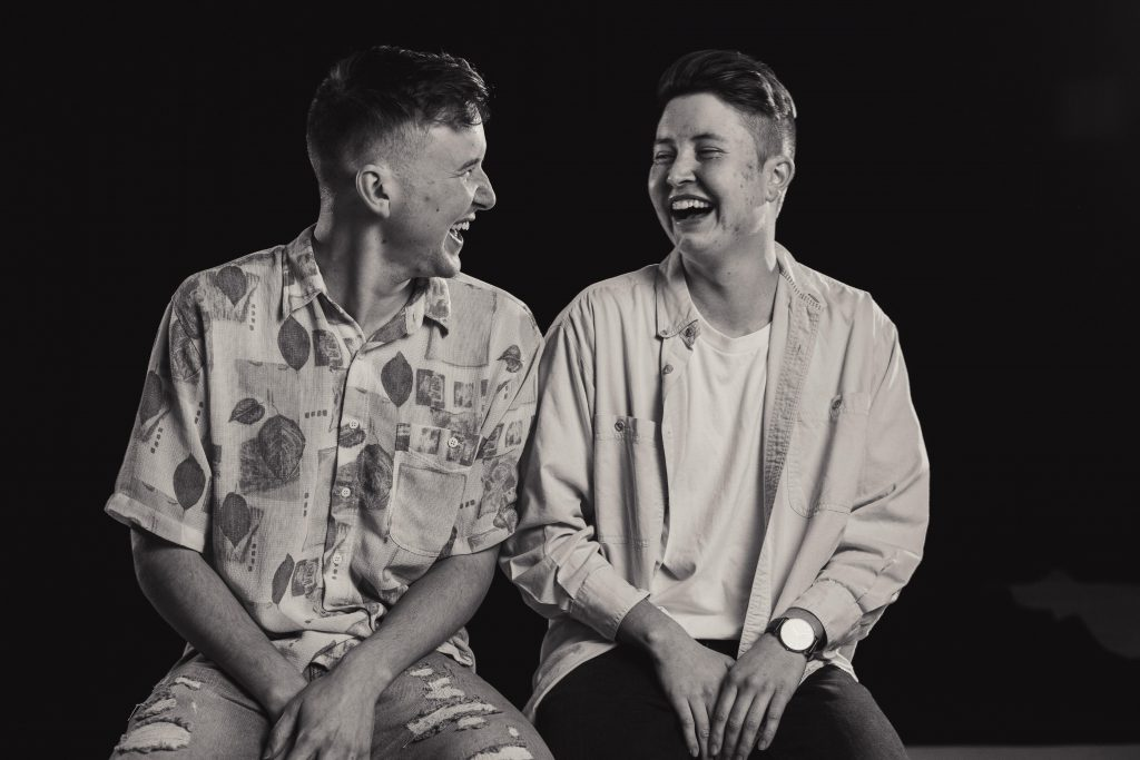Black and white portrait of two young men setting side by side and laughing.