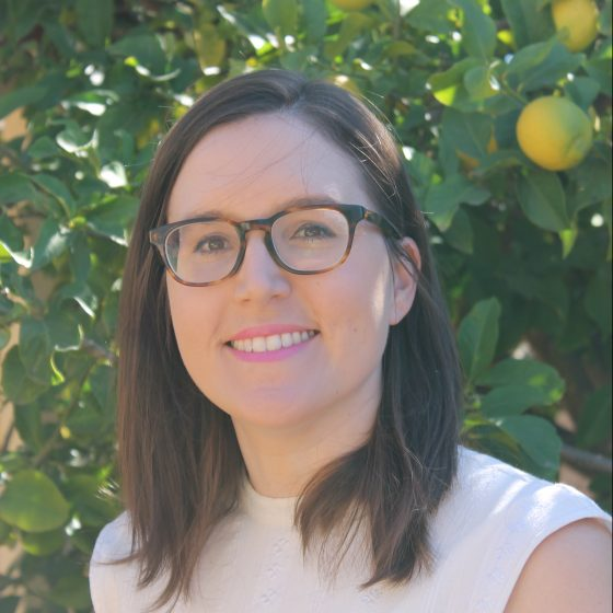 A portrait of a woman with brown hair wearing glasses