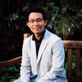 Photo of Chris Lin sitting on a wooden bench at UWA in front of beautiful green leaves. He is sitting with his hands together in a friendly pose. He is smiling. Chris wears glasses.