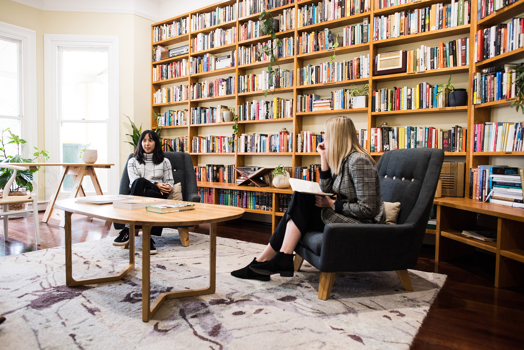 Photo of the Centre for Stories' Reading Room. It features floor to ceiling bookshelves covered with books and pot plants. Two women sit in armchairs in front of the shelves.