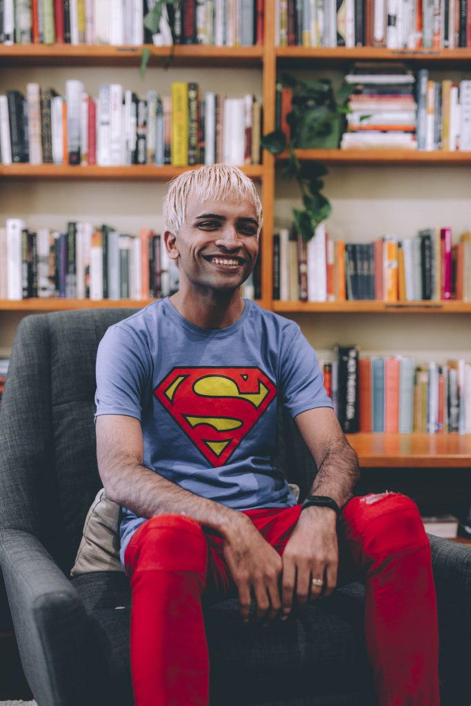 A man wearing a Superman T-shirt sitting smiling