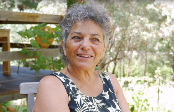 A smiling, middle-aged woman with short, curly grey hair sits outside in a lush, green garden.