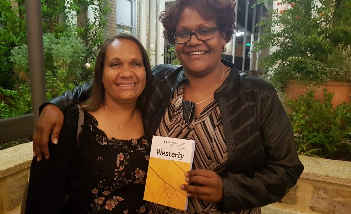 """Two women stand side by side smiling at the camera. One of them is holding a yellow and white book which says """"Westerly"""" on the cover."""