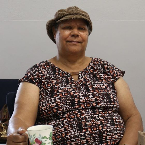 Photo of Merle Narkle Goodwin sitting at a table. She is wearing a brown hat, a floral purple and black top, and she is holing a teacup.