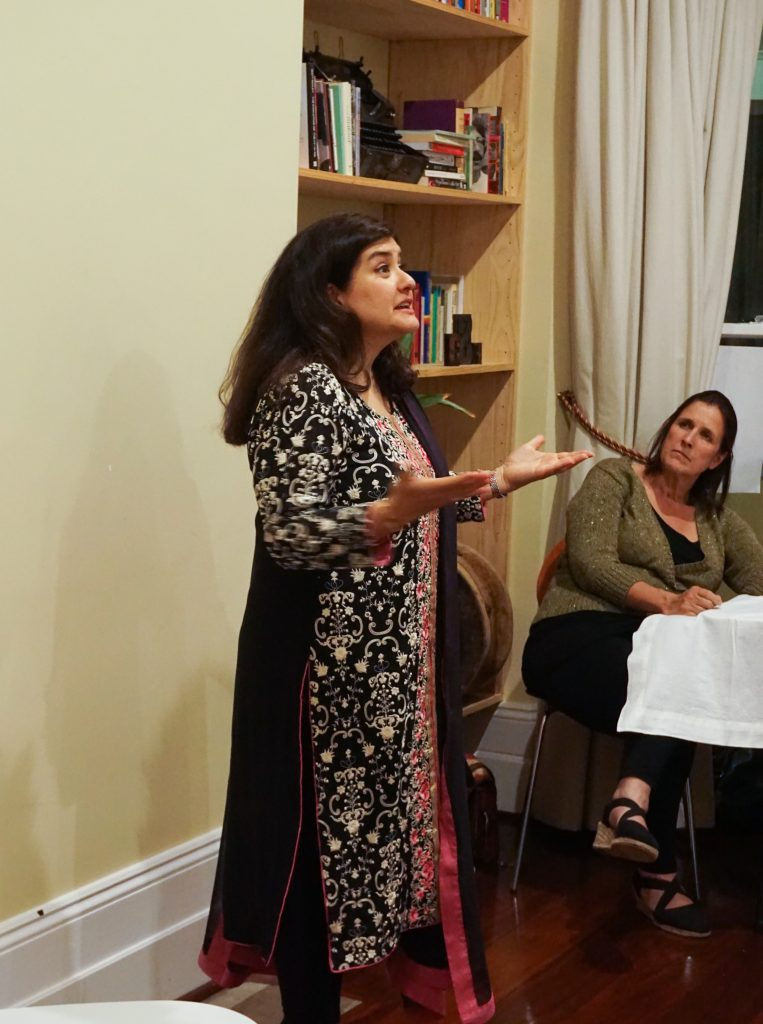 A woman standing before an audience wearing traditional Pakistani clothing. Her hands are before her in an act of expression.