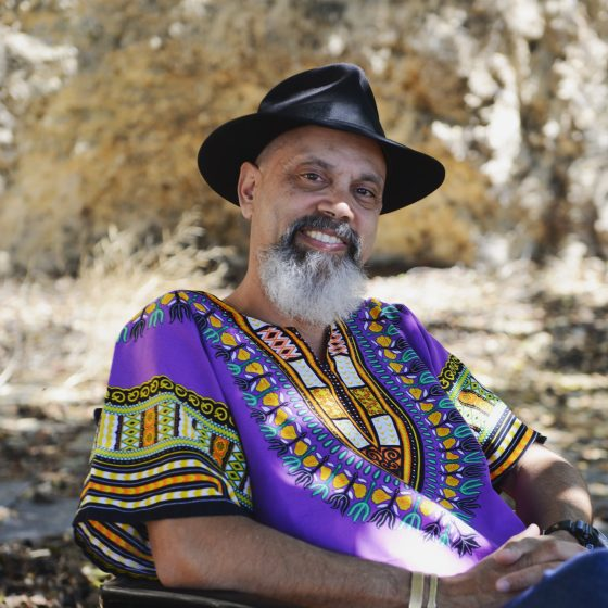 A man sits in a chair outside in the Australian bush. He wears a colourful purple and green shirt and a black fedora.