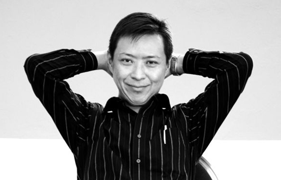 Black and white portrait of Felix Cheong sitting in a chair with his hands folded behind his head and smiling warmly at the camera.