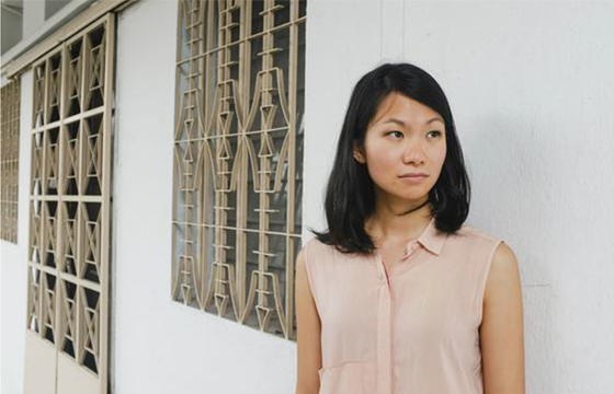 Photo of Inez Tan standing against a white wall