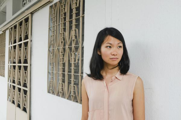 Inez Tan stands outside by a white wall