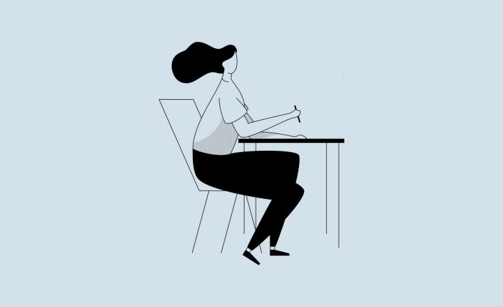 Illustration of a figure with long black hair sitting at a desk