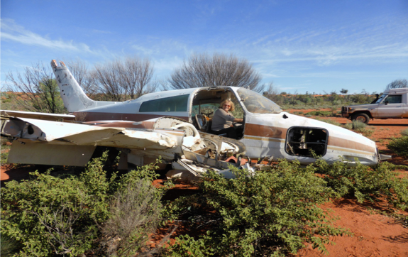 In the middle of a bushy desert, a woman sits inside the cockpit of an aircraft. This aircraft crashed here. No one was killed.