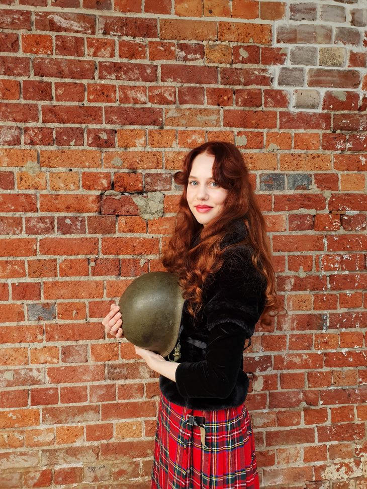 Photo of a young woman holding a WWII helmet in front of a red brick wall