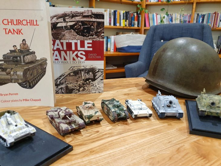 A collection of WWII memorabilia displayed on a table, including model tanks, books and a helmet