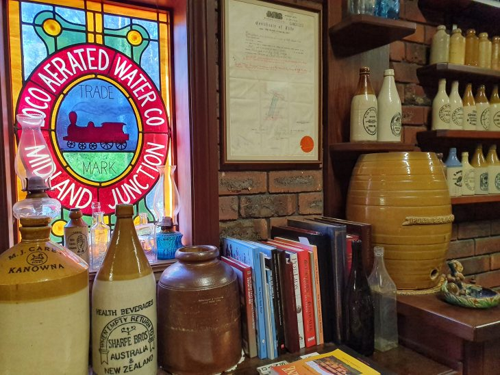 Display of various collectibles in front of a stained glass window with the words 'Midland Junction Aerated Water Co'