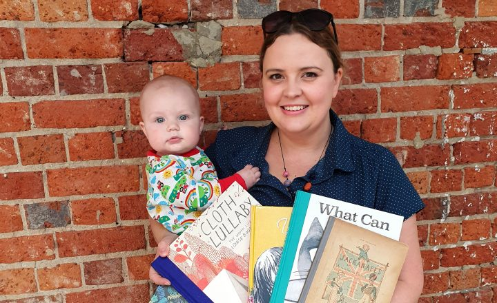 Photo of young woman with her baby and picture books in front of a red brick wall