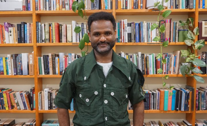 Photo of Yirga Woldeyes standing in front of the Centre for Stories bookshelves