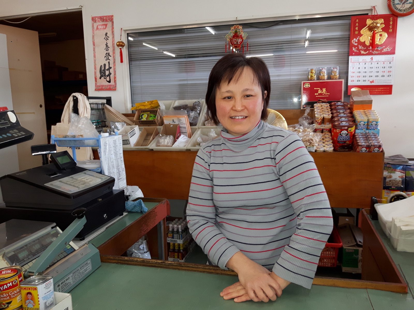 A woman smiling behind the counter of her mini mart in Fremantle.