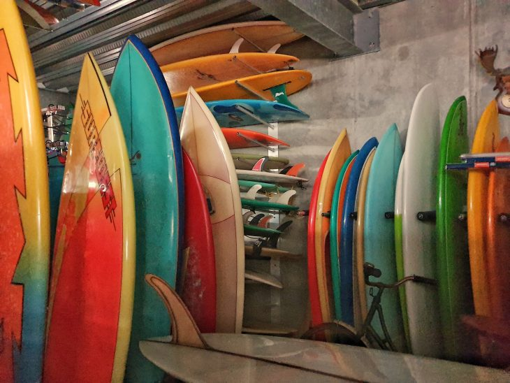 Photo of Wayne Vinten's extensive and colourful surfboard collection in his garage