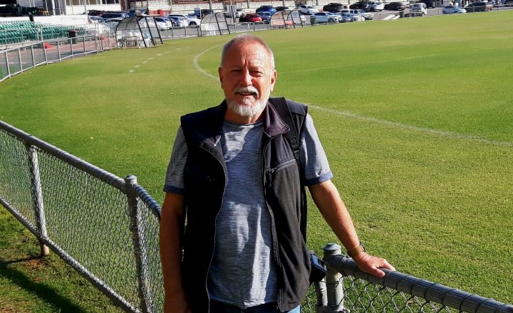 A man standing in front of a football stadium field in Fremantle.