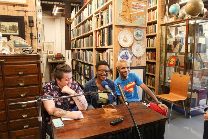 Photo of three people sitting in front of a microphone in a book shop