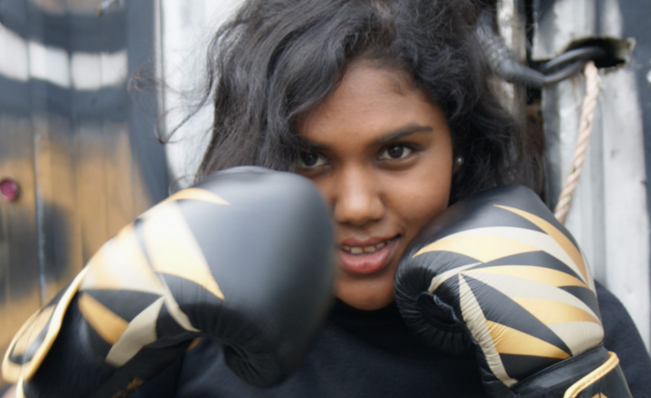 A young woman smiling at the camera. She has boxing gloves on and has them raised to her face in defensive position.