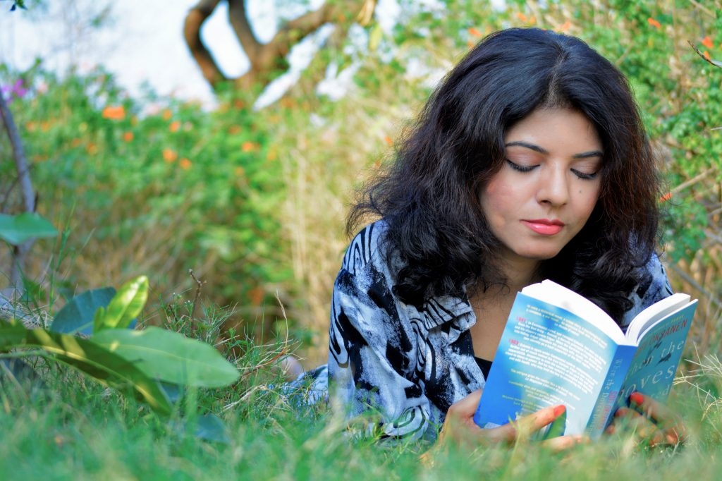Photo of Saima Afreen reading a book while laying in the grass