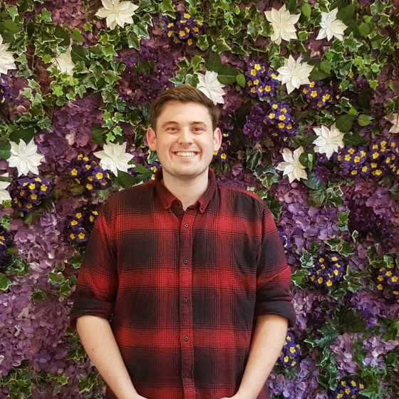 A Person wearing a flannelette shirt standing before a lovely wall of flowers.