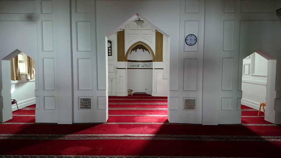 Perth Mosque: Inside. There is beautiful red carpet and delicate white arch ways. This is the prayer hall.
