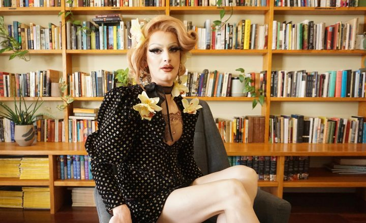 Drag queen in an armchair in front of a wall of books