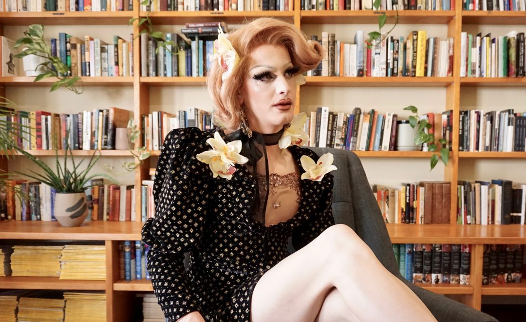 Drag performer sitting and posing in front of a bookshelf, looking upward