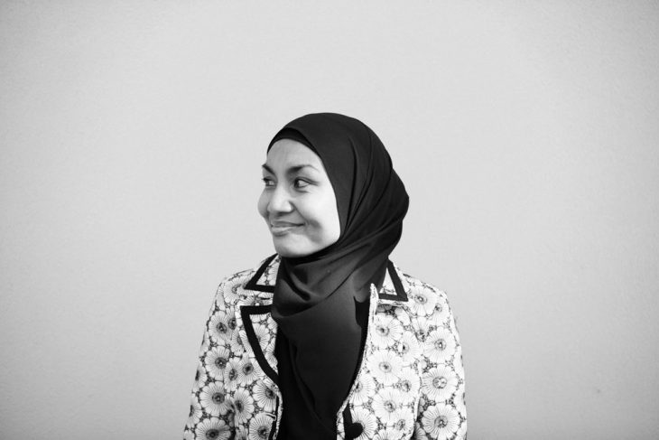 A black and white image of Raihanaty looking away from the camera and smiling.