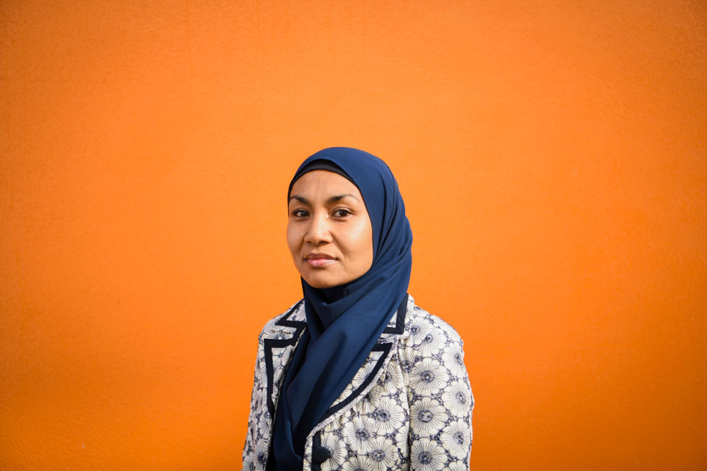 Raihanaty A Jalil stands before an orange wall. She is slightly smiling and looking at the camera.