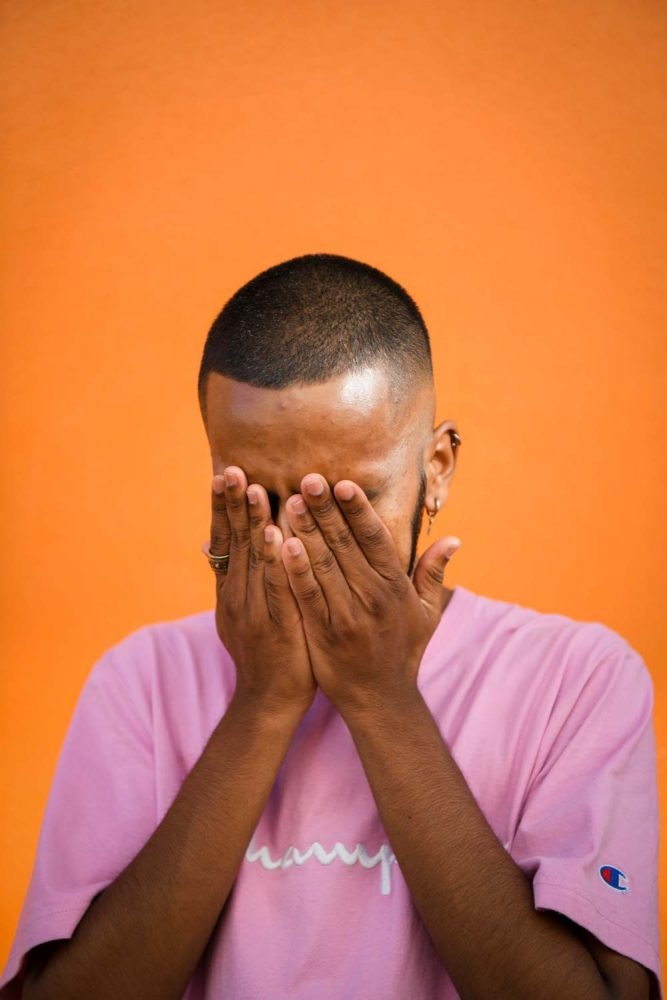 Rushil D'cruz standing laughing with his hands over his face. He is standing before an orange wall and he is wearing a pink t-shirt