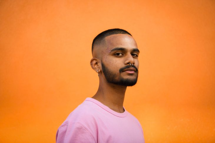 Rushil D'cruz stands turning towards the camera. He is standing before an orange wall and he is wearing a pink t-shirt