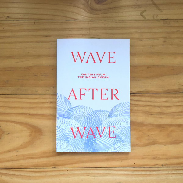 A photograph of a book against a light wood table. The book cover is mostly cream with a blue tattoo-style wave pattern at the bottom. Across the cover in bold red font it says 'WAVE AFTER WAVE'