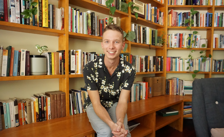 Image of intern Jordan Brunnen sitting casually on the Centre for Stories' book shelf. He's smiling at the camera.