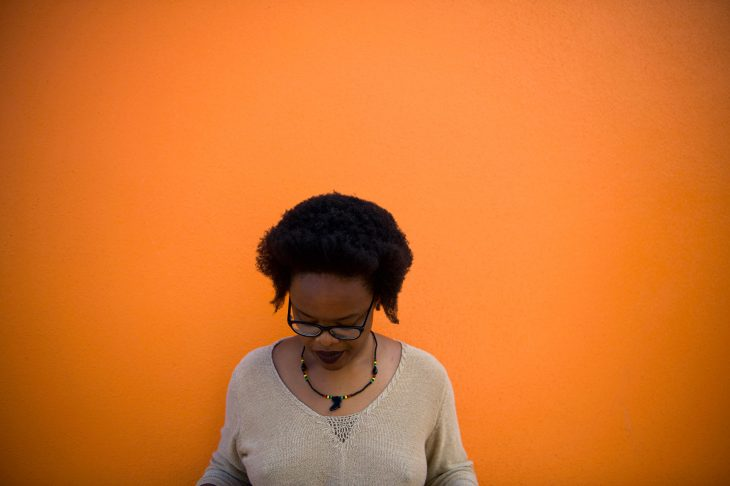 Tinashe stands before a striking orange wall laughing at something in the distance