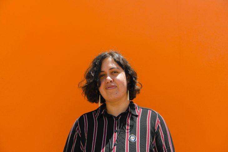 A photo of Alexander against a bright orange wall. He is wearing a red and navy striped shirt and is smiling.