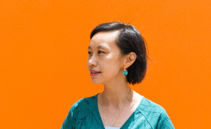 A photo of Emily against a bright orange wall. She is looking off into the distance and is wearing a green dress and green earrings.