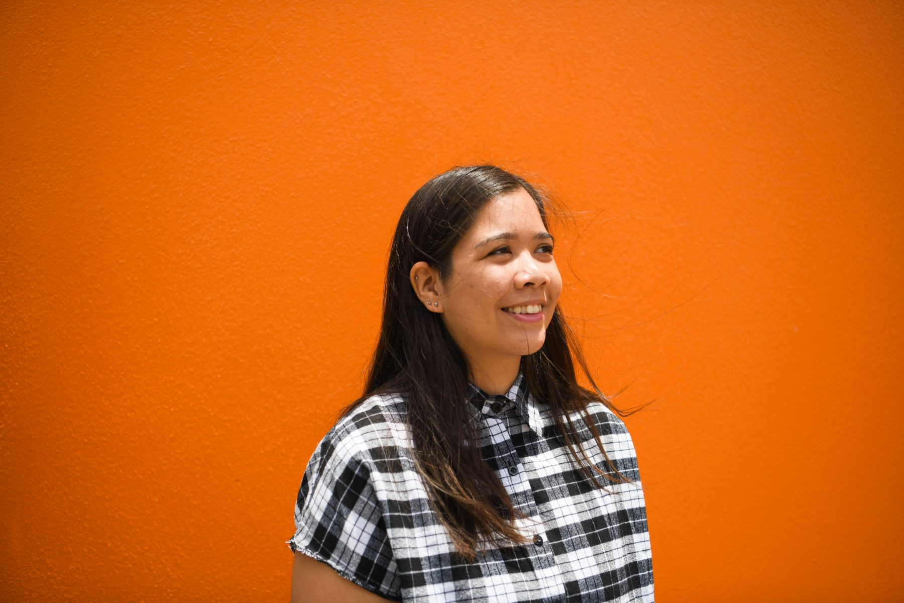 A photogrpah of Kaya standing by a bright orange wall. They have a checkered shirt on and they are smiling.